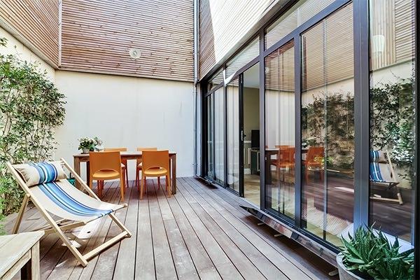 patio-en-bois-avec-reflecteur-terrasse-devant-les-baies-vitrees